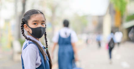 Portrait Asian children girl wear  mask to protect PM 2.5 dust and air pollution. Portrait of Thai student wearing protection mask  bad weather, pm2.5 concept background