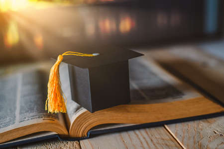 Graduate or Education knowledge learning study abroad concept: Graduation cap on opening textbook in old library