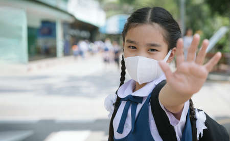 Portrait Asian children girl wear mask to protect PM 2.5 dust and air pollution. Portrait of Thai student wearing protection mask bad weather, concept of Corona virus quarantine,Covid-19