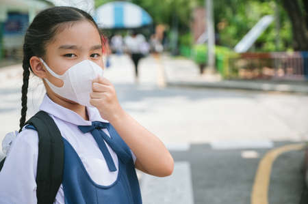Back To School. Asian children girl wear mask to  protection for coronavirus(covid-19) in the school . Portrait of Thai student wearing protection mask bad weathe. infection control concept.