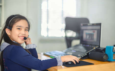 asian girl student wear headphone watch  listen online course communicate by conference video call. . Homeschooling and distance learning ,online ,internet protect from COVID-19 viruses.