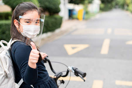 Back to school. asian child girl wearing face mask and giving thumb up with backpack biking a bicycle and going to school .Covid-19 coronavirus pandemic.New normal lifestyle.Education concept.