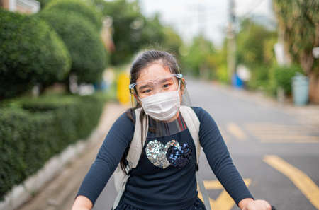 Back to school. asian child girl wearing face mask with backpack biking a bicycle and going to school .Covid-19 coronavirus pandemic.New normal lifestyle.Education concept.
