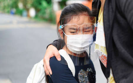Back to school. asian pupil girl wearing face mask with backpack hugging her mother crying first day go to school. Covid-19 coronavirus pandemic.New normal lifestyle. Education concept. Stockfoto