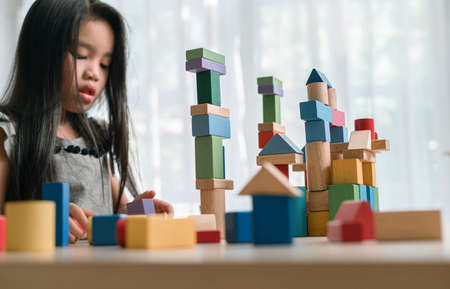 Happy little  girl playing game  building constructor tower from multicolored wooden blocks. learning and development background concept.
