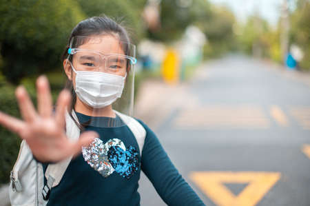 Back to School. Schoolgirl wearing medical face mask with backpack for Virus show stop hands gesture for stop coronavirus outbreak.Covid19 coronavirus, New normal,