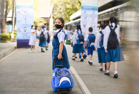 Portrait of Asian child in school uniform wearing face mask with school bag and social distancing protect from coronavirus covid-19. Back to school for new normal lifestyle concept. Stockfoto