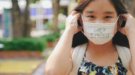 Back to school. asian child girl wearing face mask with backpack  going to school .Covid-19 coronavirus pandemic.New normal lifestyle.Education concept. Stockfoto