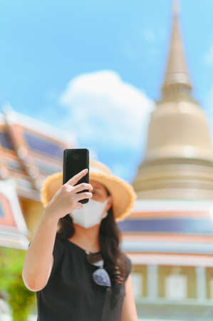 asian woman with mask enjoy happy take a photo selfie  in Wat thai. New normal travel lifestyle after virus covid concept. Stockfoto