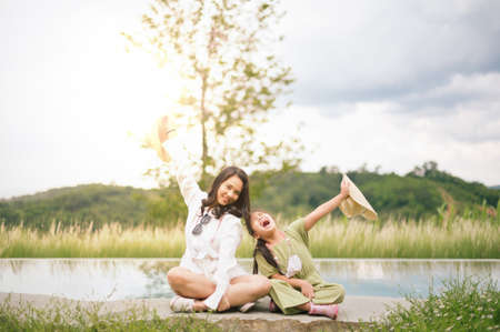 Mother and daughter having fun  in summer. Happiness and harmony in family life. Beauty nature scene with family outdoor lifestyle.