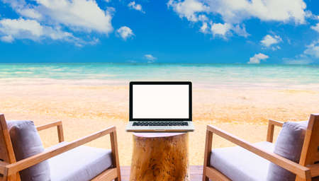 Laptop with blank screen on Empty space  on table with beautiful beach and tropical sea background