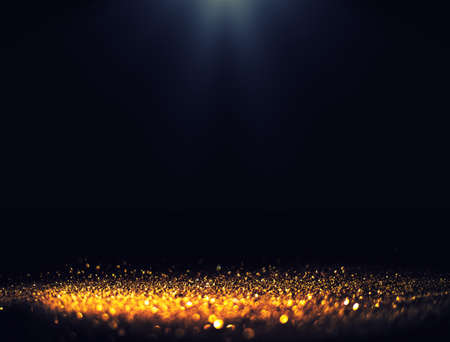 Black background with spotlight to Luxurious gold glitter sparkling background Фото со стока