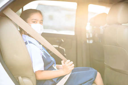 Asian kid girl student wearing mask to protect the coronavirus Covid-19 outbreak situation before go to school. Get ready to school concept. Фото со стока