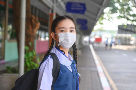 Back to school. asian child girl wearing face mask with backpack going to school .Covid-19 coronavirus pandemic.New normal lifestyle.Education concept. Фото со стока