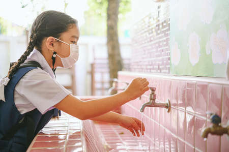 Asian student washing hands at the outdoor wash basin in the school. Preventing Contagious diseases, Plague. Kids health, protecting the virus Covid - 19 , Saving water, Cleaning, Running water.