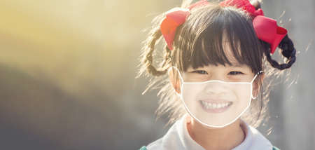 Little chinese girl wearing face mask  happy at school.