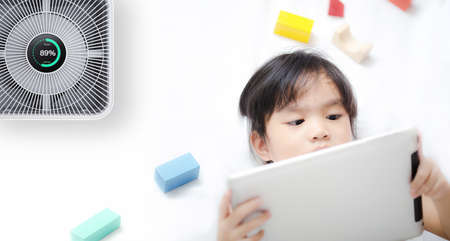 Little girl using tablet in room with modern air purifier