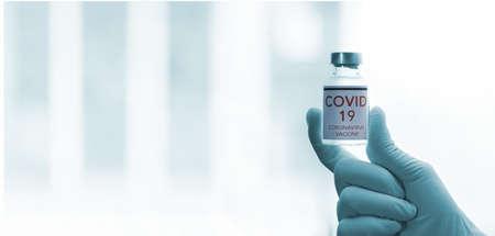 Coronavirus Vaccine concept in hand of doctor blue vaccine jar. Vaccine Concept of fight against coronavirus. Фото со стока