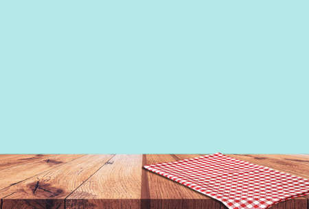 Empty wooden table with red checked tablecloth over blue wall background