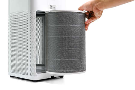 Man hold a old Filter of  the air purifier check with change filter in side air purifier for dust removal efficiency on white background