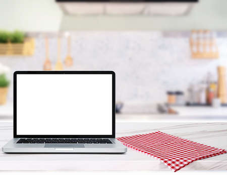 Modern computer,laptop with blank screen on Wood table top on blurred kitchen background