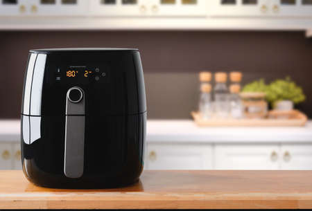 Air fryer machine cooking potato fried in kitchen.  Lifestyle of new normal cooking.