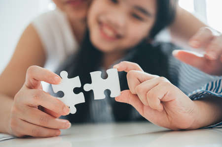 Happy family, Asian daughter playing jigsaw puzzle with her mother for family concept, Adult woman teaches child to solve puzzles, , success and strategy concept Foto de archivo