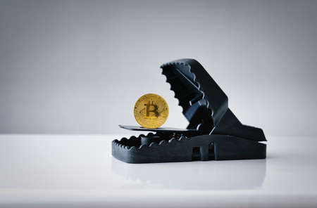 Mousetrap with gold bitcoin on wood table . Concept risks and dangers of investing to bitcoin