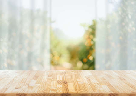 Empty of wood table  on blur abstract garden with sunlight and curtain window , product display, Ready for product montage.