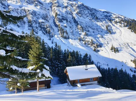 Small chalet covered with snow in Swiss alps