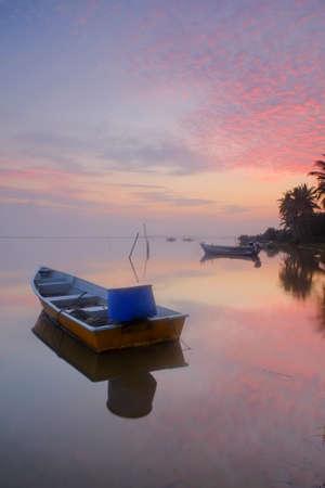 colorful sunrise: A boat during a colorful sunrise.