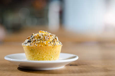 Corn muffin with poppy, sesame and sunflower seeds on a plate with blurred background
