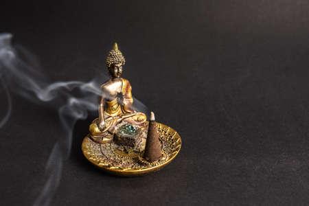 Buddha incence holder with burning cone. Meditation and yoga atmosphere 스톡 콘텐츠