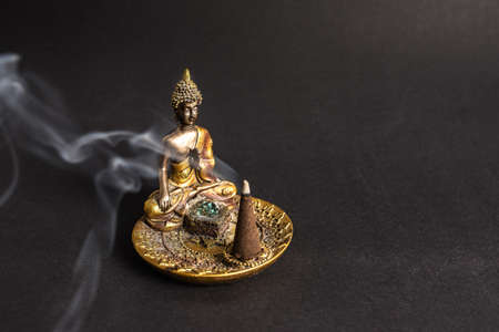 Buddha incence holder with burning cone. Meditation and yoga atmosphere Standard-Bild