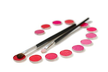 positioned: Make-up brushes and red eye shadows positioned as a palette
