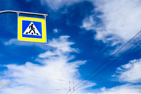 against: pedestrian crossing sign against the dramatic cloudy sky