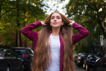 capelli lunghi: young beautiful woman in violet jacket with long hair standing in the green city street with blurred cars on both sides Archivio Fotografico