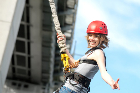 beautiful young woman in a helmet hanging on a rope after the bungee jump against the sky Banco de Imagens