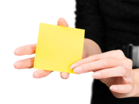 memory stick: Beautiful woman hands with blurred silhouette holding blank yellow memo stick. Isolated on white with clipping path
