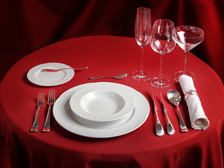 the etiquette: Red table with dinner set. Professional banquet table setting