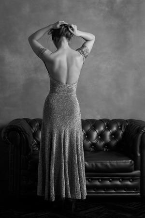 Schwarz-Weiß-Rückansicht der eleganten Frau im Abendkleid mit offenem Rücken posiert auf Vintage-Leder-Couch und strukturierte Grunge Hintergrund