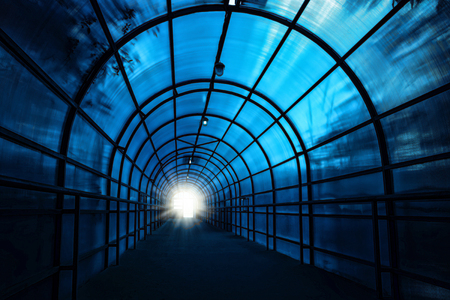 Dark blue sinister tunnel with shadows on the walls and the light at the end of it