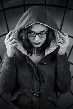 Sinister black and white portrait. Girl in the hood with gaze over her glasses and skull tattoo on the finger. On abstract dark stained-glass background Stock Photo