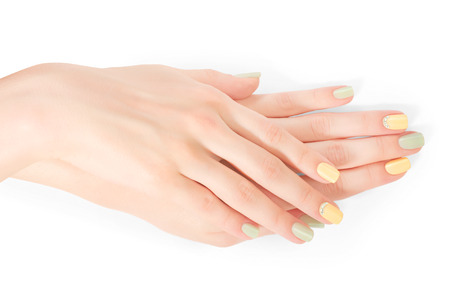 shellac: Close-up of woman hands with pastel colored shellac manicure and rhinestones. Isolated on white with clipping path
