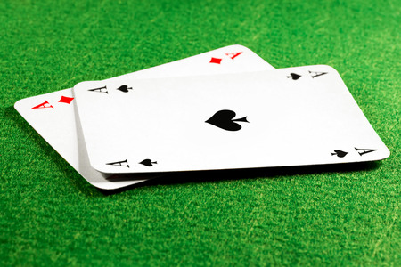 aces: Two aces on green felt casino table, ace of spades on top. Selective focus on the spade symbol