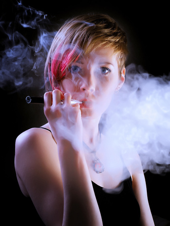 Elegant woman with eccentric hairstyle smoking e-cigarette with cloud of smoke. In cool color