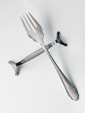 Close-up of victorian silver fork on silver knife rest. On white background