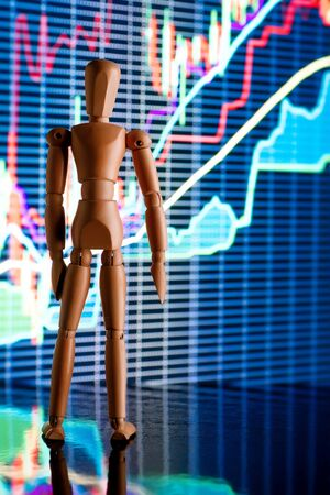 analisys: Wooden dummy character looking at complex stock market graph. Business novice, education and analisys concept