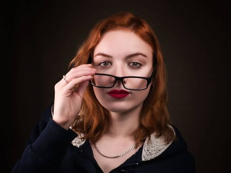 Beautiful nerd girl or young woman looking over eyeglasses. Vision, skepticism, evaluation, seduction, education and people concept