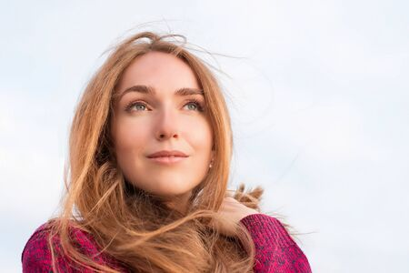 Serene beautiful woman with long hair fluttering in the wind. Outdoor portrait. Looking up at the distance, low point view Stock Photo